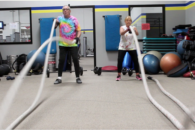 two adults doing rope workout